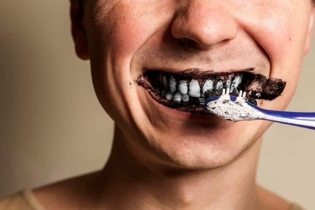 person brushing teeth with charcoal toothpaste