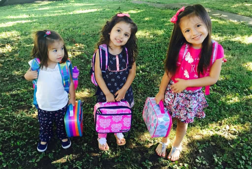 three elementary-aged girls holding lunchboxes and ready to go back to school